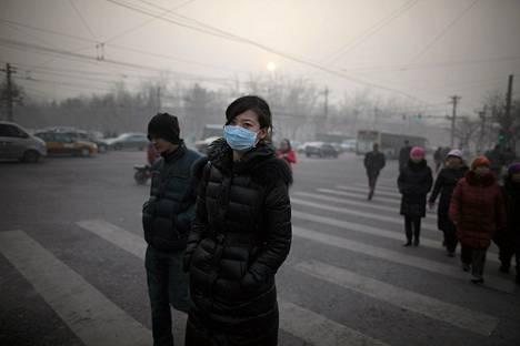 Moni suojautui saasteilta käyttämällä maskia kulkiessaan kadulla Pekingissä.