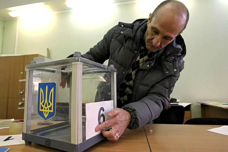 Virkailija asetteli vaaliuurnaa paikoilleen Kiovassa lauantaina.