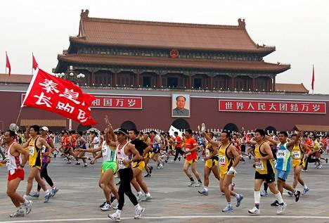Pekingin maratonin osallistujat ohittavat puhemies Maon kuvan Tiananmenin aukiolla 2009.