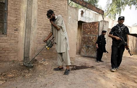 Turvallisuusviranomaiset tutkivat metallipaljastimella paikkaa, jossa räjähti pommi Peshawarassa Pakistanissa maanantaina.