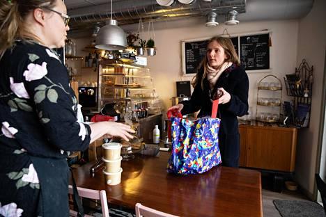 Ravintoloitsija Johanna Sauramäki (vas.) myi keittoa ja leipiä Sanni Marttiselle, joka tuli maanantaina noutamaan lounasta perheelleen Saurahuone-kahvilasta Käpylässä.