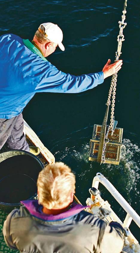 Tutkimusalus Muikun kansimies Jari Puhakka (vas.) ja perämies Jukka Kettunen nostavat merestä näytteen pohjaeläintutkimusta varten.