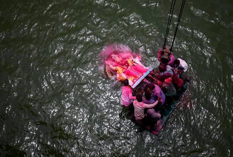 Ganesh-jumalan patsas pudotetaan Sabarmati-jokeen Ganesh Chaturthi -festivaalin päätöspäivänä tiistaina Intian Ahmedabadissa.