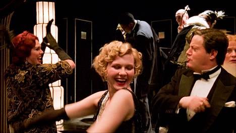 Oneida-jahdilla juhlitaan kuin viimeistä päivää. Kuvassa Elinor Glyn (Joanna Lumley, vas.), Marion Davies (Kirsten Dunst) ja Charlie Chaplin (Eddie Izzard).