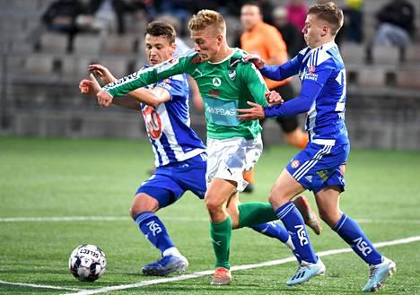 IFK Mariehamnin Gustaf Backaliden yritti edetä HJK:n Kaan Kairisen ja Ivan Tarasovin (oik.) puristuksessa.