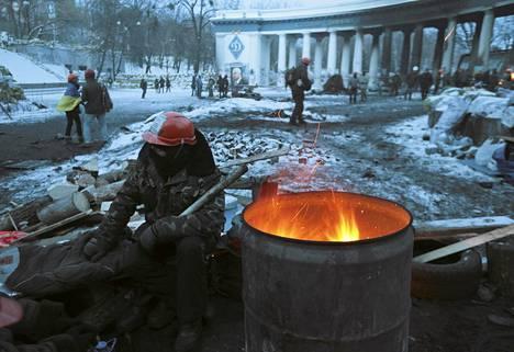 Opposition mielenosoittaja lämmittelee Kiovan keskustassa keskiviikkoiltana.