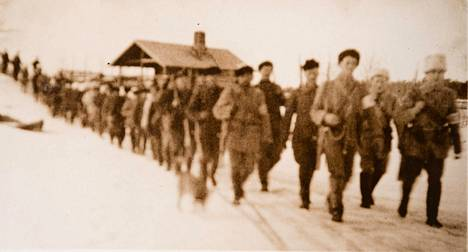 Kajaanin sissit marssivat Kinnin kylässä kevään 1918 taisteluiden aikaan. Joukkoon kuului myös lukiolaispoika Urho Kekkonen.