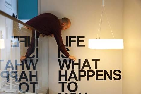 """""""Elämä on sitä, mitä tapahtuu sillä aikaa, kun teet muita suunnitelmia"""", muistuttavat portaikon seinään liimatut kirjaimet. Talon tuleva asukas John Hart lisää liimaa repsottavaa kirjainta."""