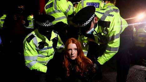Poliisit ottamassa kiinni Patsy Stevensonia, joka osallistui murhatun Sarah Everardin muistotilaisuuteen Lontoossa viime lauantaina. Miespoliisien kovat otteet ovat herättäneet paljon kritiikkiä.