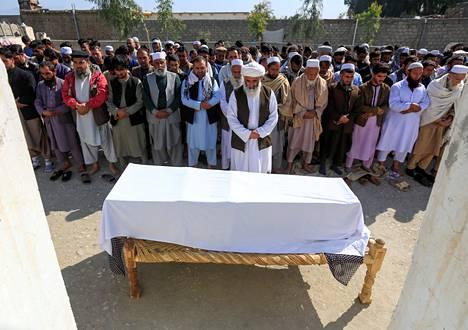 Miehiä rukoili ammutun naistoimittajan ruumisarkun äärellä Jalalabadissa maaliskuun alussa.