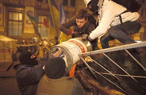 Ukrainan mielenosoittajat nostivat keskiviikkona öljy-yhtiö Castrolin tynnyriä barrikadille pääkaupunki Kiovan Itsenäisyydenaukiolla.