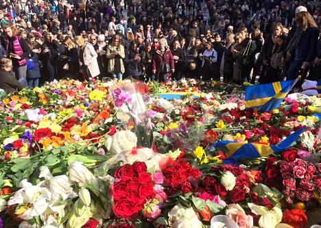 Ihmiset jättivät kukkia Sergelin torin rappusille Tukholmassa sunnuntaina.