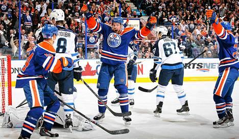 Edmontonin Jesse Joensuu (kesk.) tuulettaa osumaansa NHL:n avauskierroksella Winnipegin verkkoon.