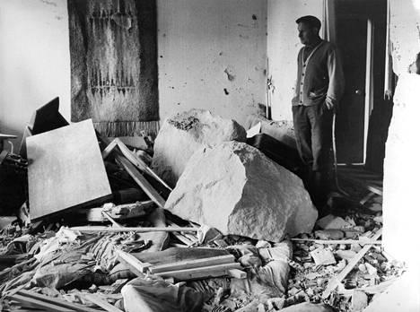 Sähköasentaja Onni Milen seisoo naapurinsa olohuoneessa, jonne oli sinkoutunut kivenlohkareita.