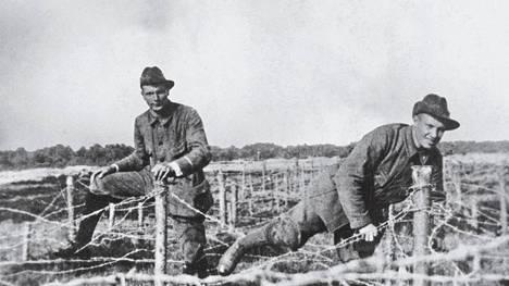 Jääkärit Verner Gustafsson, myöhemmin kenraali, ja Kosti Sundberg, sittemmin reserviupseerikoulun ensimmäinen johtaja, ylittävät piikkilankaestettä partiopuvuissaan ns. Pfadfinder-kurssilla keväällä 1915.