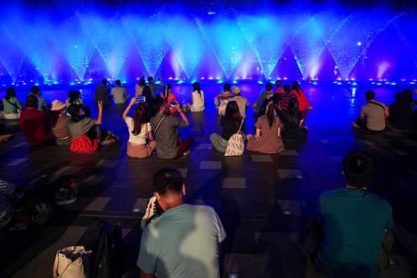 Ihmiset katsoivat suihkulähteitä ostoskeskuksessa, kun uudenvuoden lähtölaskennan juhlat ja ruuhkaiset tapahtumat oli kielletty koronavirustaudin leviämisen takia Bangkokissa Thaimaassa.