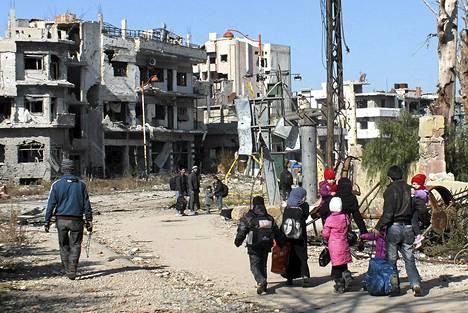 Ihmiset kävelivät tapaamispaikalle Homsin piiritetyssä kaupungissa sunnuntaina. YK ja Syyrian Punainen Puolikuu evakuoi kaupunkilaisia tänään maanantaina kolmatta päivää.