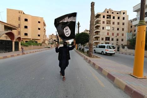 Aseistautunut taistelija heilutti Isis-lippua Syyrian Raqqassa järjestön kukoistuksen päivinä kesällä 2014.