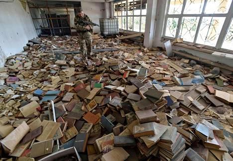 Ukrainalaissotilas tutkii hylättyä ja vandalisoitua kirjastoa Marinkan kaupungissa, joka sijaitsee Donetskin kapinallisalueen lähistöllä.