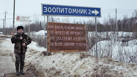 """Pavel Krimov saapui Štšelkanovon kaatopaikkaa vastustavien paikallisten leiriin. Riimimuotoon kirjoitetussa kyltissä lukee: """"Vallanpitäjät vakuuttelevat meille, että mitään lakeja ei rikota, että tämä paskasta tehty kaatopaikka on luotu kaikkien lakien mukaan."""""""
