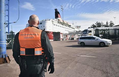 Ahvenanmaalainen rajavartija seurasi autolautasta purkautuvaa liikennettä Långnäsin satamassa 23. maaliskuuta.