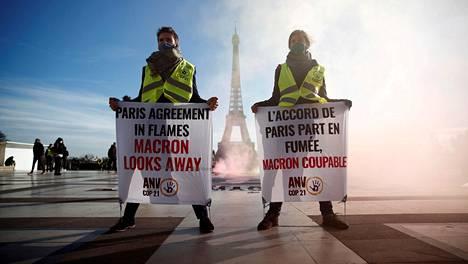 Ilmastomielenosoittajat kokoontuivat joulukuussa Eiffel-tornin luo Pariisissa. Banderolleissa lukee, että Pariisin ilmastosopimus on liekeissä mutta Macron katsoo pois.