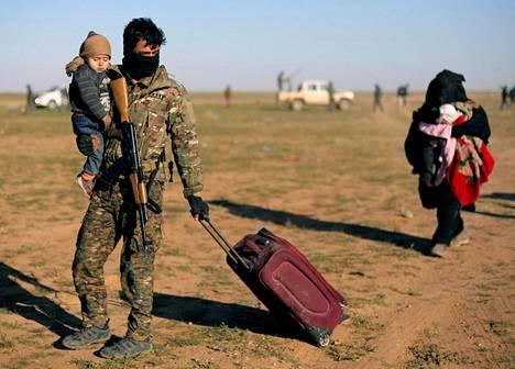 Yhdysvaltain tukemien SDF-joukkojen sotilas kantoi perjantaina lasta lähellä Baghouzin kylää Syyriassa.
