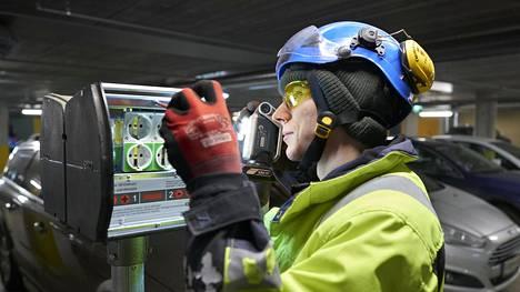 Lämmitystolpat muutetaan sähköautojen lataukseen sopiviksi taloyhtiössä Kalasatamassa. Asentaja Jesse Lehtola tekee muutostyöt sähkötolppiin.