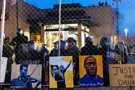 Mielenosoittajat jättivät Brooklyn Centerin kaupungin poliisiasemalle kyltit poliisin käsiin kuolleiden Elijah McClainin ja George Floydin muistoksi 14. huhtikuuta 2021.