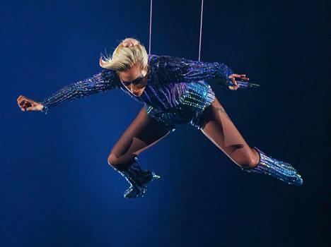 Lady Gaga laskeutuu areenan keskelle narujen varassa kattorakenteista.