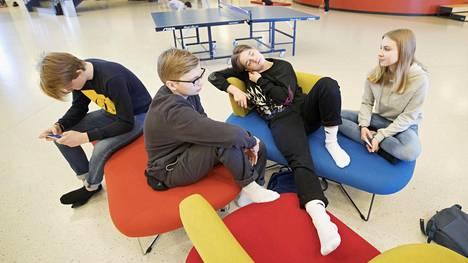 """Kahdeksasluokkalaiset Aukusti Kaasinen (vas.), Viljami, Aku  Kuosmanen ja Aino Pirnes  odottelivat ulkovälitunnin alkamista Ritaharjun koulussa. """"Lisää sohvia  ja lupa olla sisällä"""", he toivoivat."""