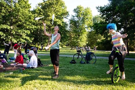 Eero Härö heittelee keiloja ja Inka Mikkonen harjoittelee yksipyöräisellä ajamista.