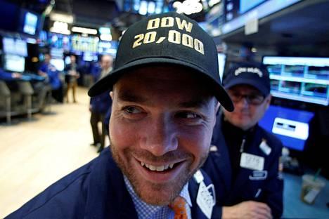 Osakevälittäjät New Yorkin pörssissä panivat keskiviikkona päähänsä Dow 20 000 -lippalakit juhlistaakseen historiallista päivää.