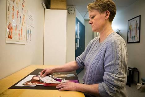 Annika Lehtinen lajittelee lehtileikkeitä sen mukaan, näkyykö kuvassa vasen vai oikea käsi.