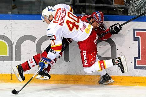Jokerien Markus Nordlund (numero 40) taklaa HIFK:n Ville Peltosta, joka  tuupertui jäähän.