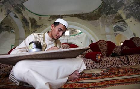 Nuori mies opetteli ulkoa Koraania puutaulun avulla ja valmistautui paastokausi ramadaniin Libyan Bengasissa tällä viikolla. Uskonto on yhä tärkeä libyalaisille.