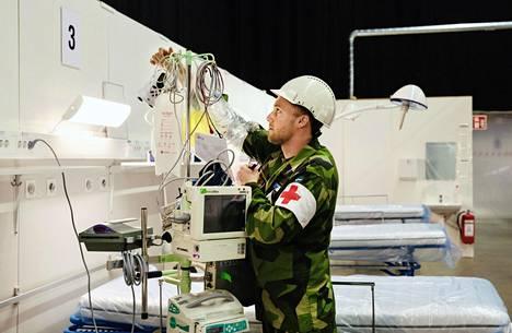 Markus Larsson kokosi laitteistoa kenttäsairaalassa Stockholmsmässan-messukeskuksessa keskiviikkona.