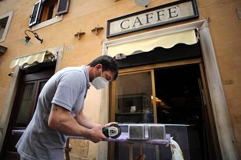 Avaamista odottavan kahvilan edessä valmisteltiin suojapleksin asentamista Roomassa lauantaina.