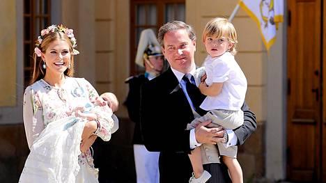 Prinsessa Madeleine ja hänen puolisonsa Christopher O'Neill lapsineen kuvattiin Drottningholmin palatsin pihalla. madeleinen sylissä lepää Adrienne, Christopherin sylissä on Nicolas. Maassa leikkii Leonore.