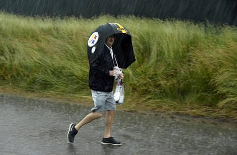 Golffani suojautui Pittsburgh Steelers -joukkueen sateenvarjoon Yhdysvaltain avoimen golfturnauksen avauspäivänä 16. kesäkuuuta.