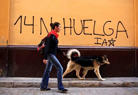 Nainen ohitti koiransa kanssa tiistaina Espanjan Sevillassa seinään kirjoitetun ilmoituksen, jossa mainostettiin keskiviikkona pidettävää yleislakkoa.