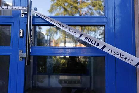Poliisin eristysnauhaa rapun ovessa.
