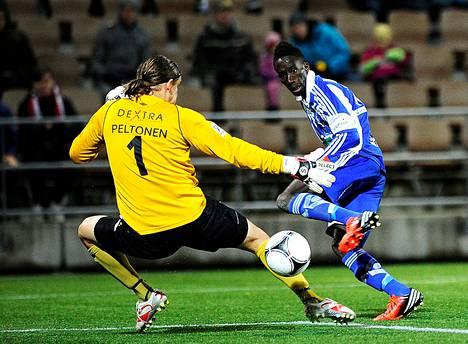 HJK:n Demba Savage sijoittaa taitavasti pallon maaliin ohi Hongan maalivahdin Tuomas Peltosen.