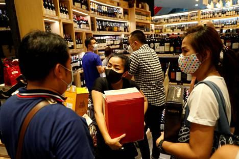 Ihmisiä alkoholiostoksilla Bangkokissa torstaina ennen kymmenen päivän myyntikieltoa.
