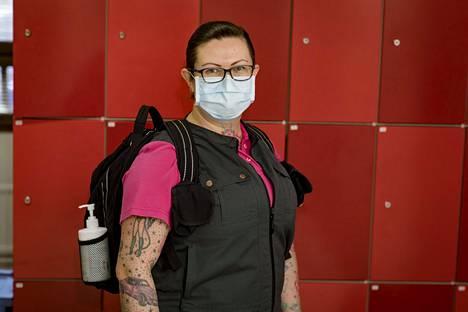 Itä-Helsingissä työskentelevä lähihoitaja Sanni Seppälä pukeutuu kotihoitajan töissä kasvosuojukseen. Mukana on myös käsidesiä.