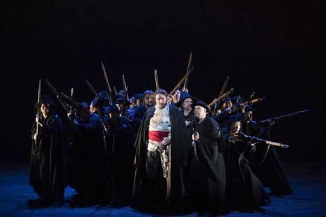 Ferrando (keskellä etualalla) laulaa ensimmäistä aariaa, kun yksi hänen taustallaan näkyvistä sotilaista raiskaa naisen (ei kuvassa) useiden muiden pidellessä naista aloillaan.