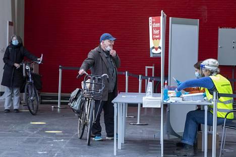 Pyöräilijät jonottivat maanantaina varhennetusti avatuille äänestyspisteille Amsterdamissa.
