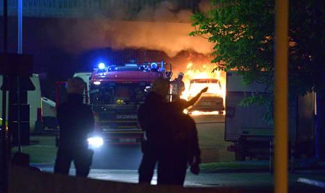 Poliisit seurasivat maanantain vastaisena yönä Husbyssä, kun palomiehet sammuttivat mellakoitsijoiden sytyttämiä autoja.