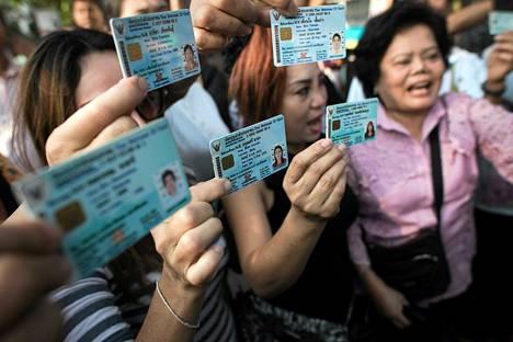 Thaimaalaiset esittelivät henkilökorttejaan Bangkokissa sunnuntaina.