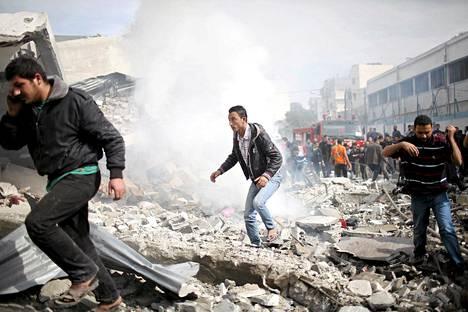 Palestiinalaismiehet juoksevat turvaan Israelin ilmaiskun aikana Gazassa sunnuntaina.